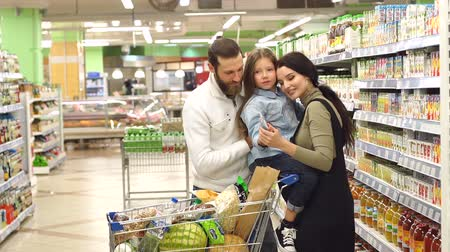 супермаркет : Portrait of happy young family with daughter in supermarket, they buy juice for child. Close-up of a young family in a supermarket with a cart full of products. Slow motion.