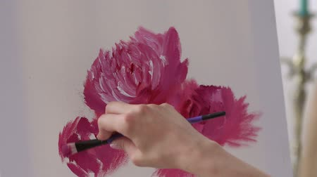 pioenroos : Close-up of the girl artist draws pink flowers on a white canvas. Close-up of a talented girl draws flowers on a white canvas at home. Stockvideo
