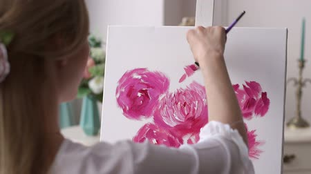 image house : A young creative girl draws flowers on a white canvas in the drawing Studio. Art. Beautiful women are creating art. Young artist painting in the house. Stock Footage