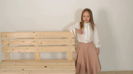 oito : Cute little girl in a white blouse and a long beige skirt posing in the Studio next to a wooden bench on a white background. Portrait of a cute girl of eight years in the Studio. Slow motion.