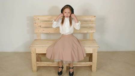 blúz : Cute little girl in vintage clothes sitting on a wooden eco-bench in a white blouse, long skirt and black hat, she poses for the camera in the Studio with a white wall. Slow motion. Stock mozgókép