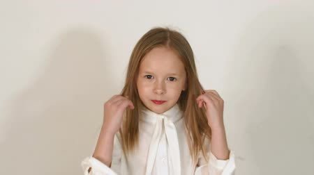 hair dress : Cute little girl with blond hair poses in the studio in front of the camera against a white wall, she straightens her hair and looks at the camera. Slow motion.
