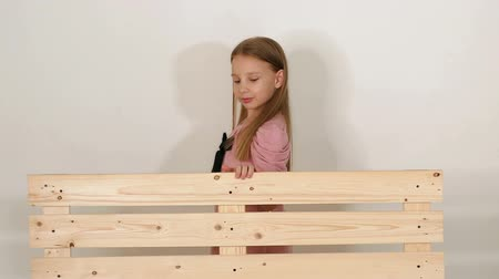 невинный : Little girl in a pink dress with a black bow, slow walking near a wooden bench and looking into the camera in the studio on a white background. The bench is made of wooden pallets. Slow motion.