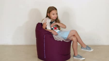 fasola : Cute little girl sitting on purple bean bag sofa for living room or other room, isolated on white background. A little girl is played in a soft chair against a white wall. Slow motion.