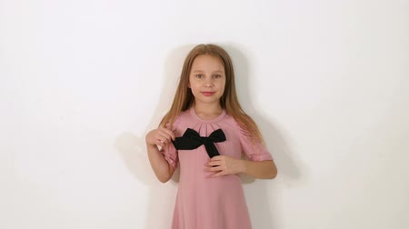 giydirmek : A little girl in a pink dress is standing against a white wall in the studio, she throws up her long hair and looks at the camera. Portrait. Slow motion. Close-up.