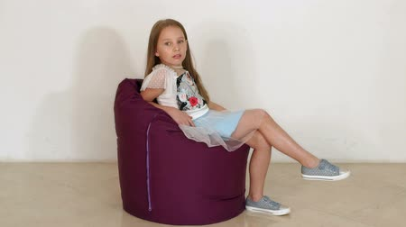 bakıyor : Cute little girl sitting on purple bean bag sofa for living room or other room, isolated on white background. A little girl is played in a soft chair against a white wall. Slow motion.