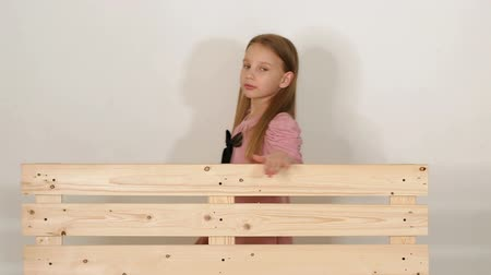 into the camera : Little girl in a pink dress with a black bow, slow walking near a wooden bench and looking into the camera in the studio on a white background. The bench is made of wooden pallets. Slow motion.