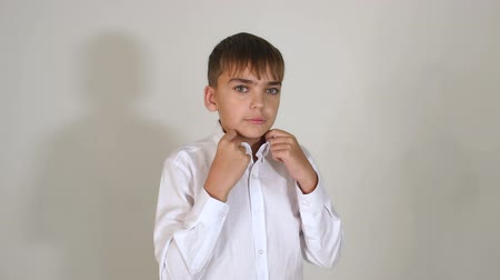 schoolkid : A small dark-haired boy with thick eyebrows posing for the camera in the Studio against a white wall. Portrait of a little boy fashion model. Slow motion.