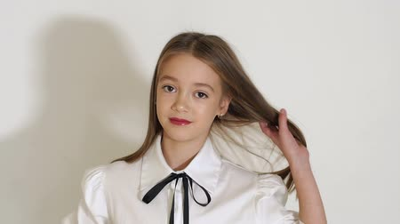 blúz : A cute teen girl in a white blouse with a black tie and long hair posing in the Studio on a white background, she straightens her hair with her hands. Slow motion. Stock mozgókép