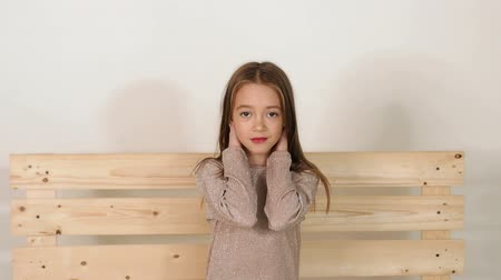 hair dress : Cute little eight-year-old girl sitting on a bench in a fashion Studio and posing for the camera, she put her head in her hands, looking at the camera and smiling. Slow motion.