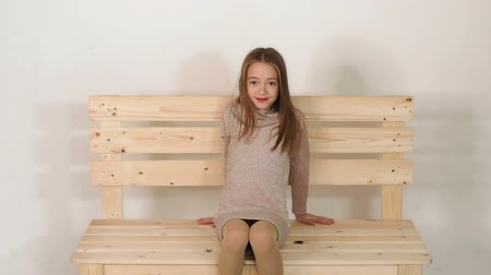 adorable : A little cute girl in a shiny jacket sits on a wooden homemade bench in the Studio with a white background, she poses for the camera. Slow motion.