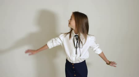 blúz : A beautiful girl of 10 years is dressed in a black skirt and a white blouse, she poses for the camera in the Studio on a white background. Slow motion. Stock mozgókép