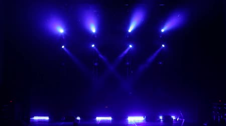 pankáč : White and blue beautiful rays of light on an empty stage before the concert. Colorful light flashing and white rays on an empty stage in the dark.