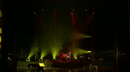 nagy felbontású : Colorful light flashing and white rays on an empty stage in the dark. Stage lighting. Light show. Stock mozgókép
