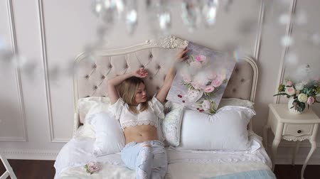 mentiras : A sexy girl in torn jeans and a white topic lies on the bed on large pillows and holds a picture with painted flowers in her hands. Art. Slow motion. Vídeos