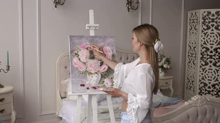 мольберт : Cute young girl draws on canvas peony flowers at home in the bedroom in a modern interior, in the background is a large bed. Slow motion. Стоковые видеозаписи