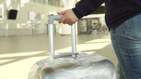 упакованный : Female hands hold the suitcase handle while standing in line at the airport. Concept of tourism and travel. Close-up. Close-up of a woman holding a suitcase which is packed in protective film. Стоковые видеозаписи
