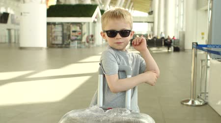utas : Portrait of a funny little boy in sunglasses and a gray t-shirt with a suitcase at the international airport. Slow motion.