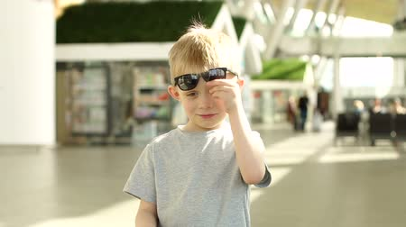 utas : Portrait of a smiling little boy in an international airport building wearing sunglasses, wearing a gray t-shirt.