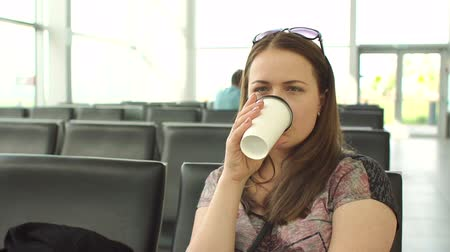 megérkezik : Young tired woman drinking coffee at the airport in a waiting room sitting on a bench, she is waiting for her flight. Travel and people concept.
