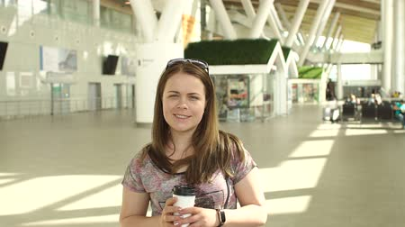 megérkezik : Young woman with luggage and coffee at the departure hall of the airport during the summer vacation. Portrait of a young girl with a Cup of coffee in a large airport lobby.
