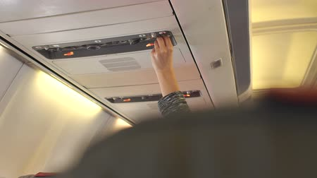 steward : Hand adjusting air conditioning in aircraft cabin. Flight attendant call button. Air conditioning in the plane.