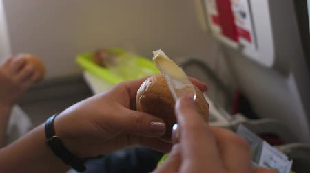 lunchen : Close-up of a woman is spreading butter on bread in a plane with a disposable plastic knife. Mom and son have lunch on the plane during the flight. Slow motion.
