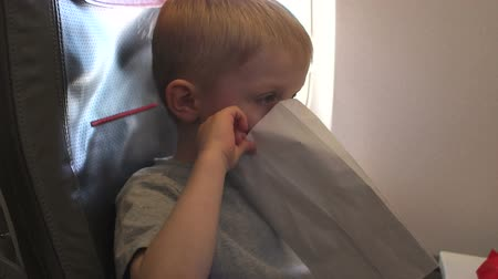 kleurplaten : Close-up portrait of a little boy on a plane, he is vomits and he is holding a special package for vomiting. The kids vomits on the plane, hes vomiting. Slow motion.