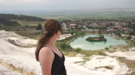 travertino : Young girl looking on travertine pools and terraces in Pamukkale. Cotton castle in southwestern Turkey. Young woman enjoying the views on travertine pools and terraces in Pamukkale. Slow motion.