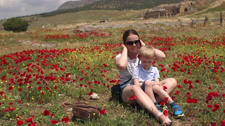 vlčí máky : Portrait of happy mom with little son in poppy field, they sit on the ground and enjoy the good weather. Beautiful view of the poppy field in Turkey on Pamukkale. Dostupné videozáznamy