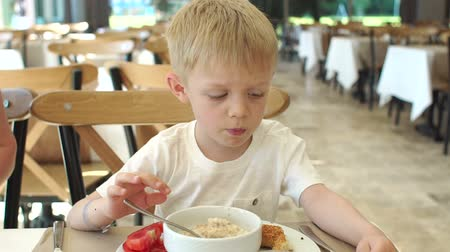 apetite : Upset little boy eating oatmeal in the restaurant, he does not want to eat porridge. Breakfast at the hotel restaurant. The child does not want to eat oatmeal for Breakfast. Slow motion.