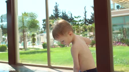 plavec : A little blond boy wraps himself in a towel after swimming in the pool. The child has frozen in the pool water, he is covered with a towel and warms up after swimming. Slow motion.