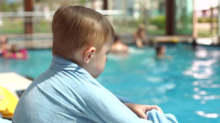 deck chairs : Portrait of a sad little boy on a lounger by the pool, he is wrapped in a blue towel. Portrait of a little boy in the pool, in the background blurred people swimming in the pool.