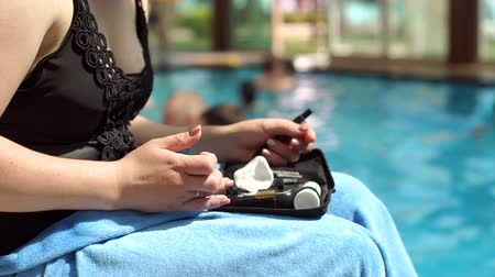 glukometr : A diabetic is testing blood glucose levels by the pool on vacation. Diabetes lifestyle, diabetic vacation at sea. Diabetes is not a hindrance to rest and an active, healthy lifestyle.