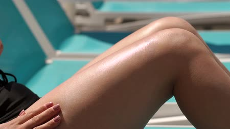 melisa : Young woman is applying sun cream on her smooth tanned legs by the pool on hot summer day. Sun Protection Factor in vacation, concept. Slow motion. Stok Video