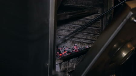 oven chicken : Close-up of a man mixing coals in a professional barbecue stove. Cooking meat or fish on the grill in the restaurant. Stock Footage