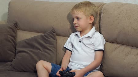 ifjabb : Close-up of a little boy playing video games with a joystick in his hands sitting on the couch at home. Slow motion. Stock mozgókép