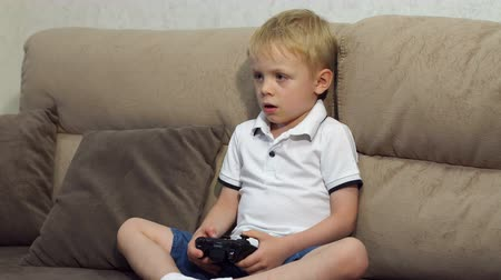 akciók : Cute boy playing video games at home. Cheerful boy sitting on a sofa and playing video games. Slow motion. High resolution.