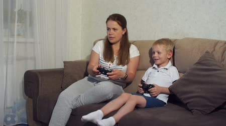 контроллер : Boy with mother sitting on sofa and playing in action game on television. Mom and son play video games at home with joysticks in their hands, they sit on the couch. Leisure. Gaming video games concept Стоковые видеозаписи