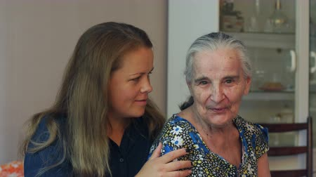 yüksek çözünürlüklü : A young woman is talking to her eighty-year-old grandmother at home, they are sitting on the couch. Young woman hugging her ninety year old grandmother. Stok Video