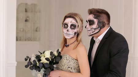 фольклор : Luxury young couple with halloween skull make-up in a dress and costume in a white room with vintage interior. Halloween face art. Halloween couple, woman and man with skull make-up. Стоковые видеозаписи