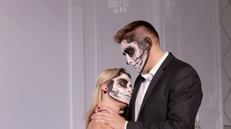 косплей : Close-up portrait of a creepy girl with makeup in the form of a skull, a man holding her neck trying to strangle. Women dressed in costume cosplay horror zombies or ghost on Halloween festival.