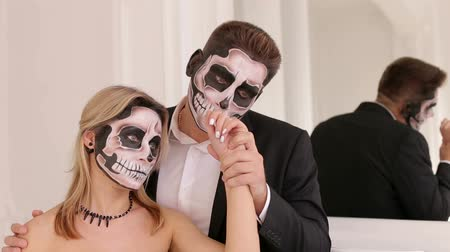 фольклор : Creepy couple of actors with scary Halloween makeup in vintage costumes on white background with beautiful mirror. A loving couple with a painted face at a Halloween party. Ghosts.