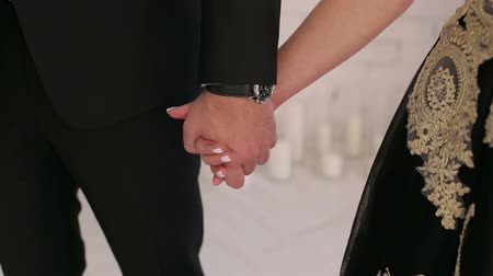 casal : Close-up of a man and woman holding hands, a girl dressed in a black-gold dress, and a man in a suit. Stock Footage