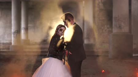 şeytan : Couple with dark skull makeup on the background of burning fire and smoke. Halloween face art. Halloween concept. Zombie. Silhouette. Slow motion.