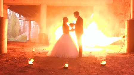 demons : Beautiful couple in wedding attire with a terrible makeup for Halloween are standing under an abandoned bridge, in the background a huge flame of of fire show. Hellfire. Slow motion. Flamethrower.