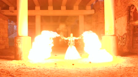 demons : A couple in wedding dresses and with skull-like makeup perform a fire show in an abandoned mansion. Halloween party, young people shoot from a fiery gun with a big flame. Fire show.