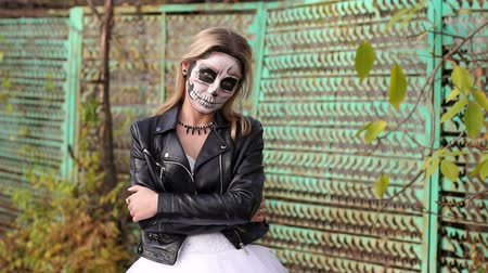 маска : A young girl with a creepy make-up in the form of a skull on her face in a wedding dress and a leather jacket on the background of an old rusty fence. Halloween. The image of the dead bride.