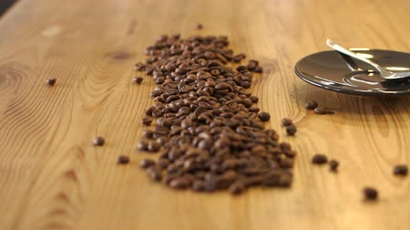 çuval bezi : Barista pours out coffee beans from a bag on a wooden table in a coffee shop. Close-up of coffee beans on a wooden surface. Slow motion.