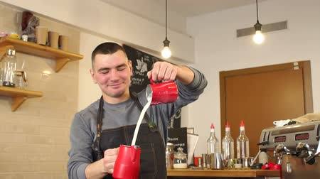 étkező : Portrait of a male Barista in a coffee shop, he dances and pours milk from bowl to bowl. The cheerful man makes a great cappuccino in the cafe, he pours the milk raised high the Cup. Slow motion.